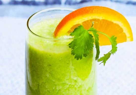 Тропический смузи из ананаса бананов листьев кориандра и апельсинового сока.
