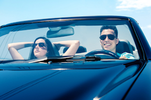 Portrait of attractive young teen Couple driving convertible.