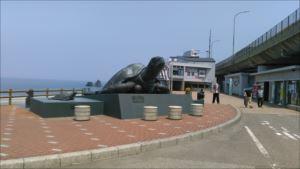 日本海をバックに首をあげている巨大亀