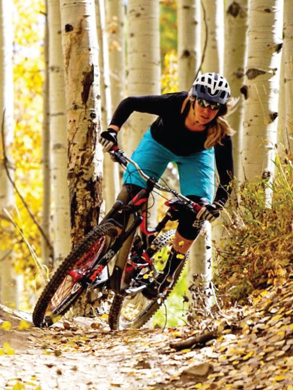 Amanda Batty riding a mountain bike through aspen forest
