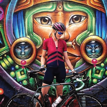 Helen Gardner with her bike in front of a mural