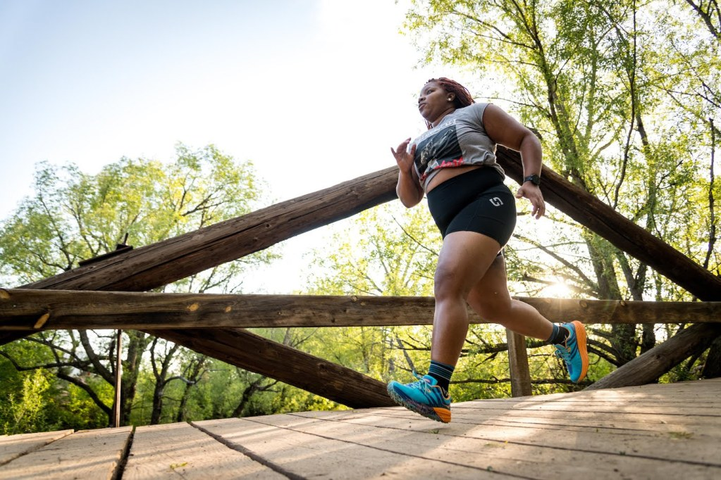 Latoya running across wooden bridge
