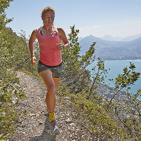 Hillary Allen trail running with mountains and lake in background