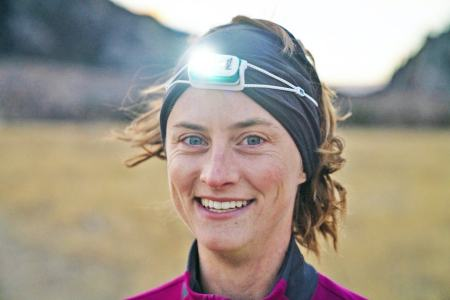 Clare Gallagher headshot, wearing a headlamp in the mountains