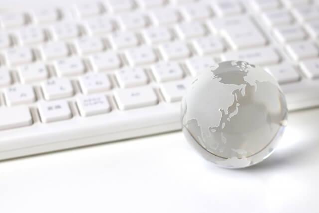 パソコンキーボードの前に,スケルトンの地球儀