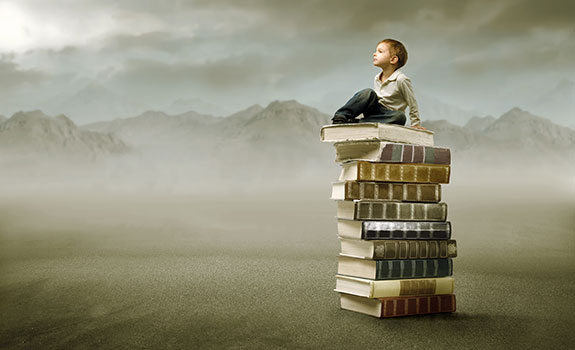 kind zittend op stapel boeken