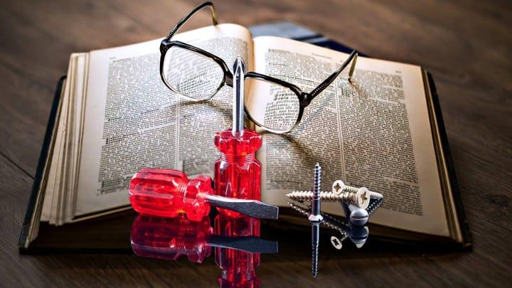 משקפיים וכלים להידוק מסגרת המשקפיים, מונחים על ספר.