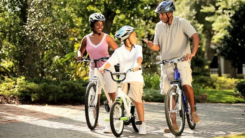 Healthy Diverse Family Bike Riding Together In Park Stock ...