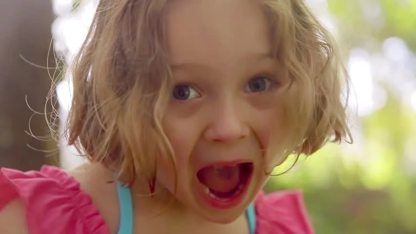 Little Girl Smiles And Opens Her Eyes And Mouth Wide In