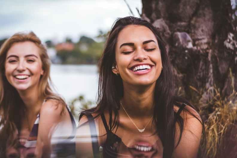 Two Divine Feminine Woman smiling dark hair big smiles happy
