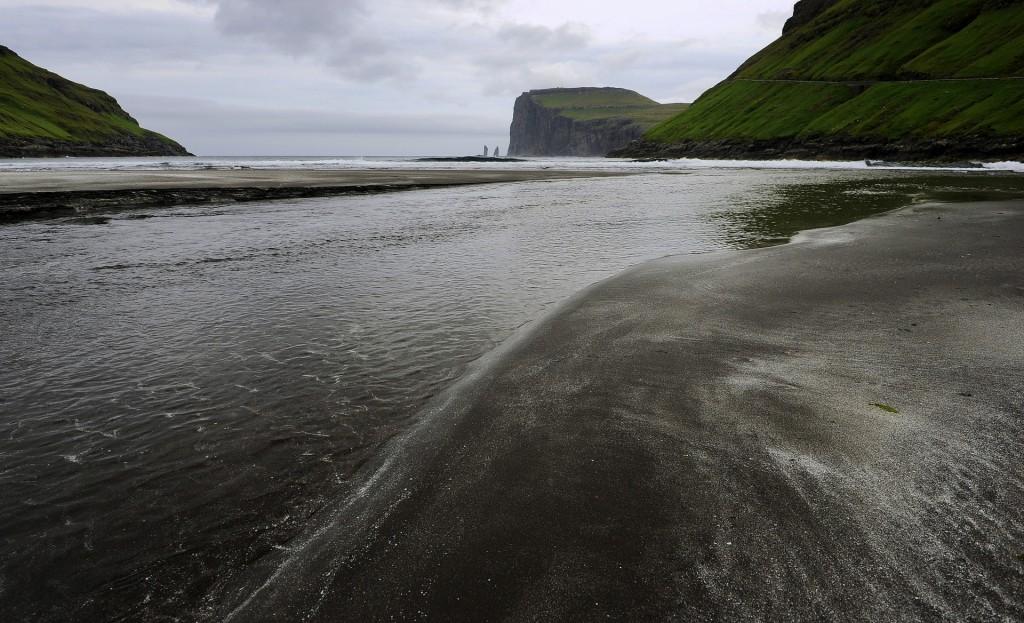 La spiaggia di sabbia nera e, a distanza, i faraglioni di