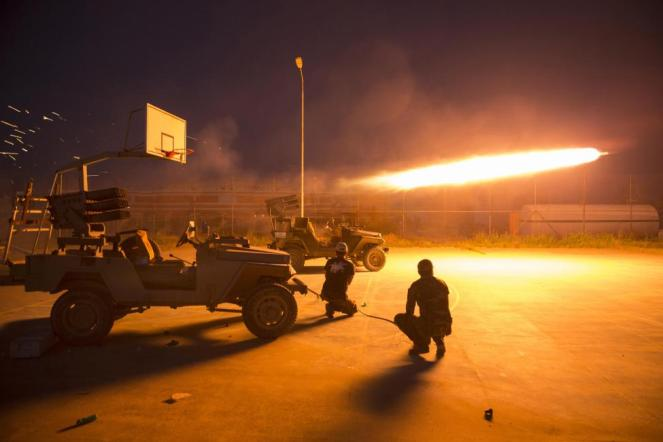 Shi'ite fighters fire a rocket during clashes with Islamic State militants in Salahuddin province, Iraq, March 1, 2015. REUTERS/Ahmed Al-Hussaini