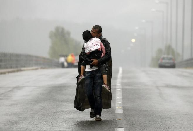 A Syrian refugee kisses his daughter as he walks through a rainstorm towards Greece's border with Macedonia, near the Greek village of Idomeni, September 10, 2015. REUTERS/Yannis Behrakis