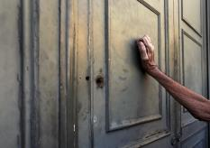A pensioner leans against the main door of a branch of the National Bank as he waits to receive part of his pension in Athens, Greece, July 7, 2015. REUTERS/Yannis Behrakis