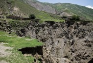 A village soon to be abandonned due to retrogressive erosion from the river below and landslides from the slope above