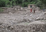 Children playing on the landslide material that buries their village