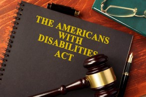 "Picture of brown notebook with title, 'The Americans With Disabilities Act."" Dark brown wood and gold gavel lying on top of the notebook. Pair of glasses lying above the book."