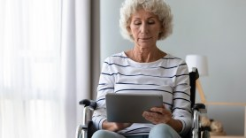 Senior lady in wheelchair, using a notebook computer.