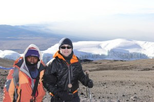 Trekker and guide walking up to Uhuru Peak in Kilimanjaro