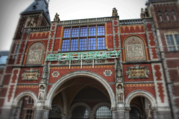 A blinking neon green sign greets visitors at the Rijksmuseum