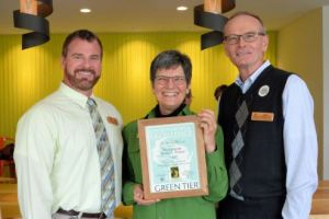 Secretary's Director JD Smith, left, and State Forester Fred Souba Jr., right, celebrate the signing of a Green Tier charter with Wisconsin Urban Wood's Executive Director Twink Jan-McMahon (Photo Credit: Wisconsin DNR)
