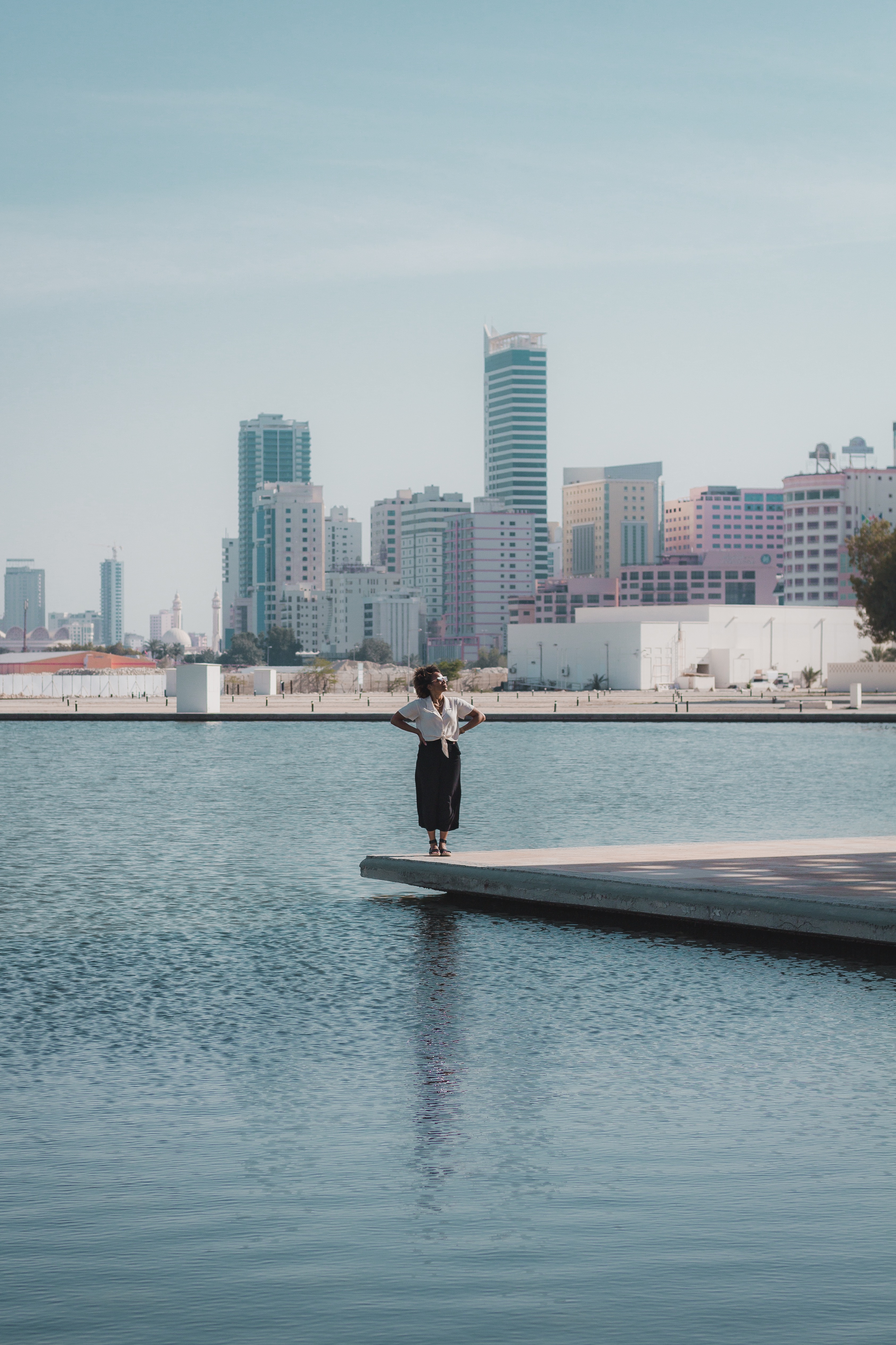 Illustrated by Sade - Woman outside the Bahrain National Theater with city skyline and water in the background