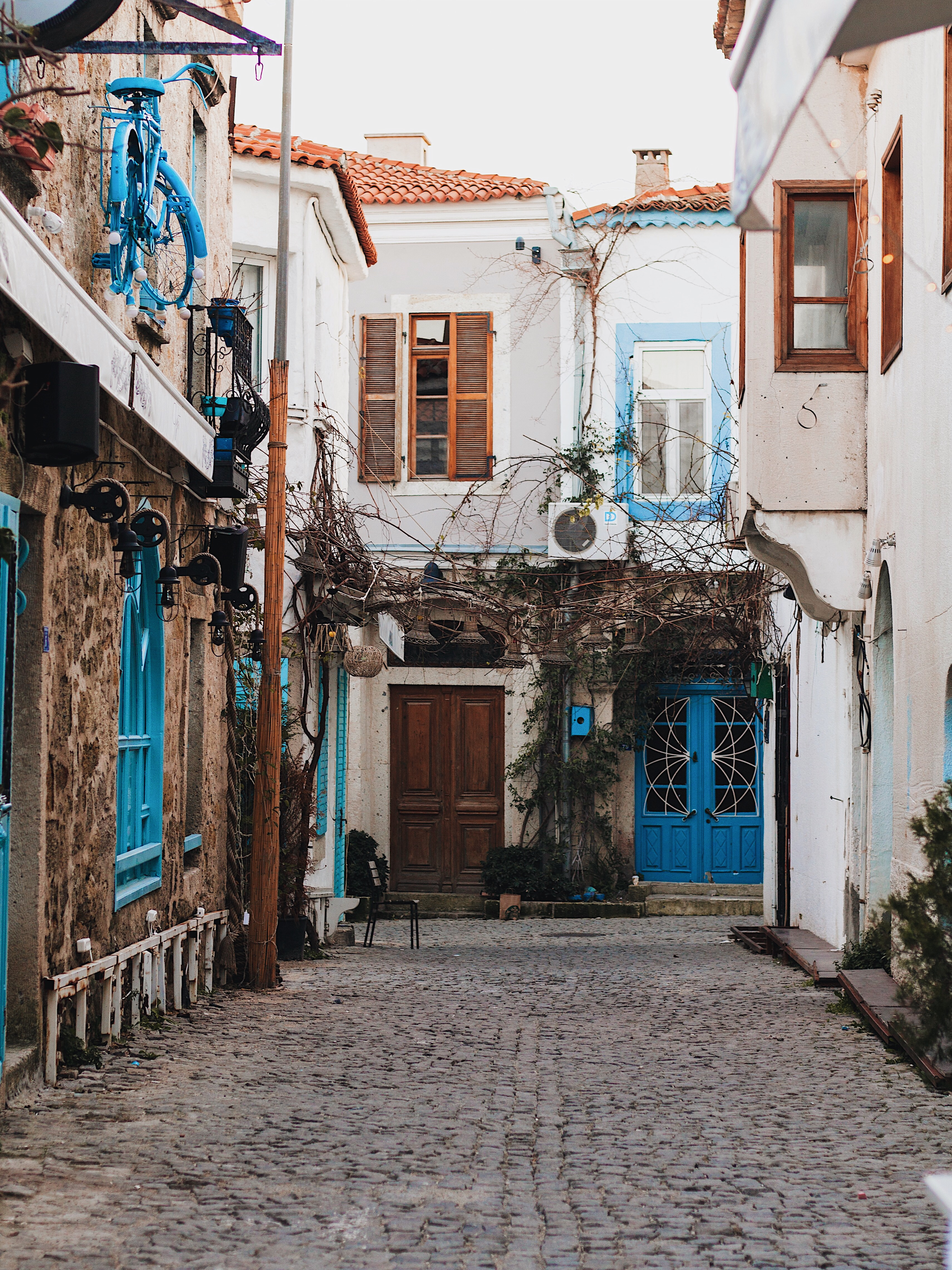 Illustrated by Sade - Blue and White House down a cobble stone street in Alacati, Izmir, Turkey
