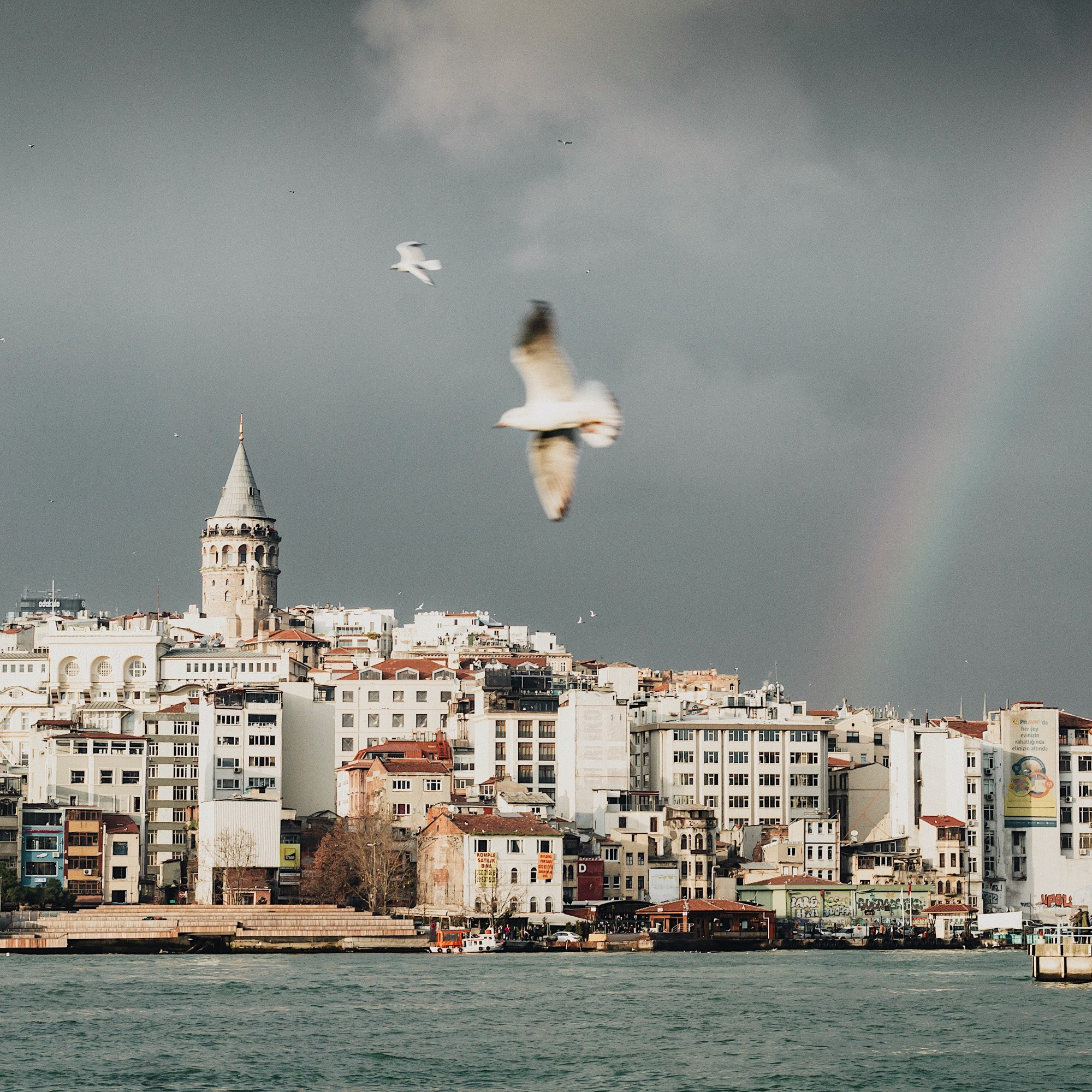 Illustrated by Sade - Rainbow, grey clouds and rain showers overlooking the Galata Tower, Istanbul, Turkey