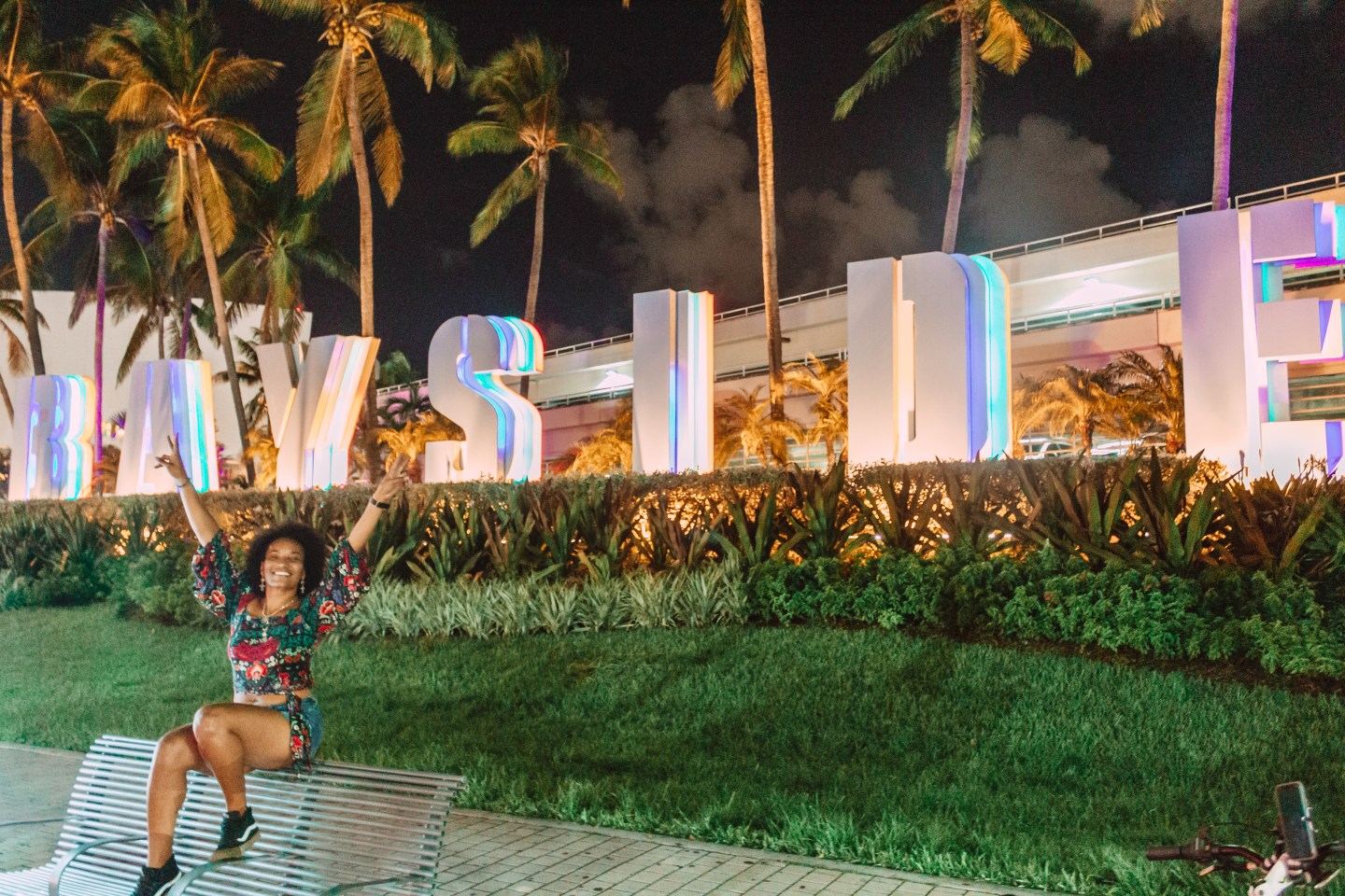 Illustrated by Sade - Woman taking photo at night in front of Bayside large sign in Miami, Florida