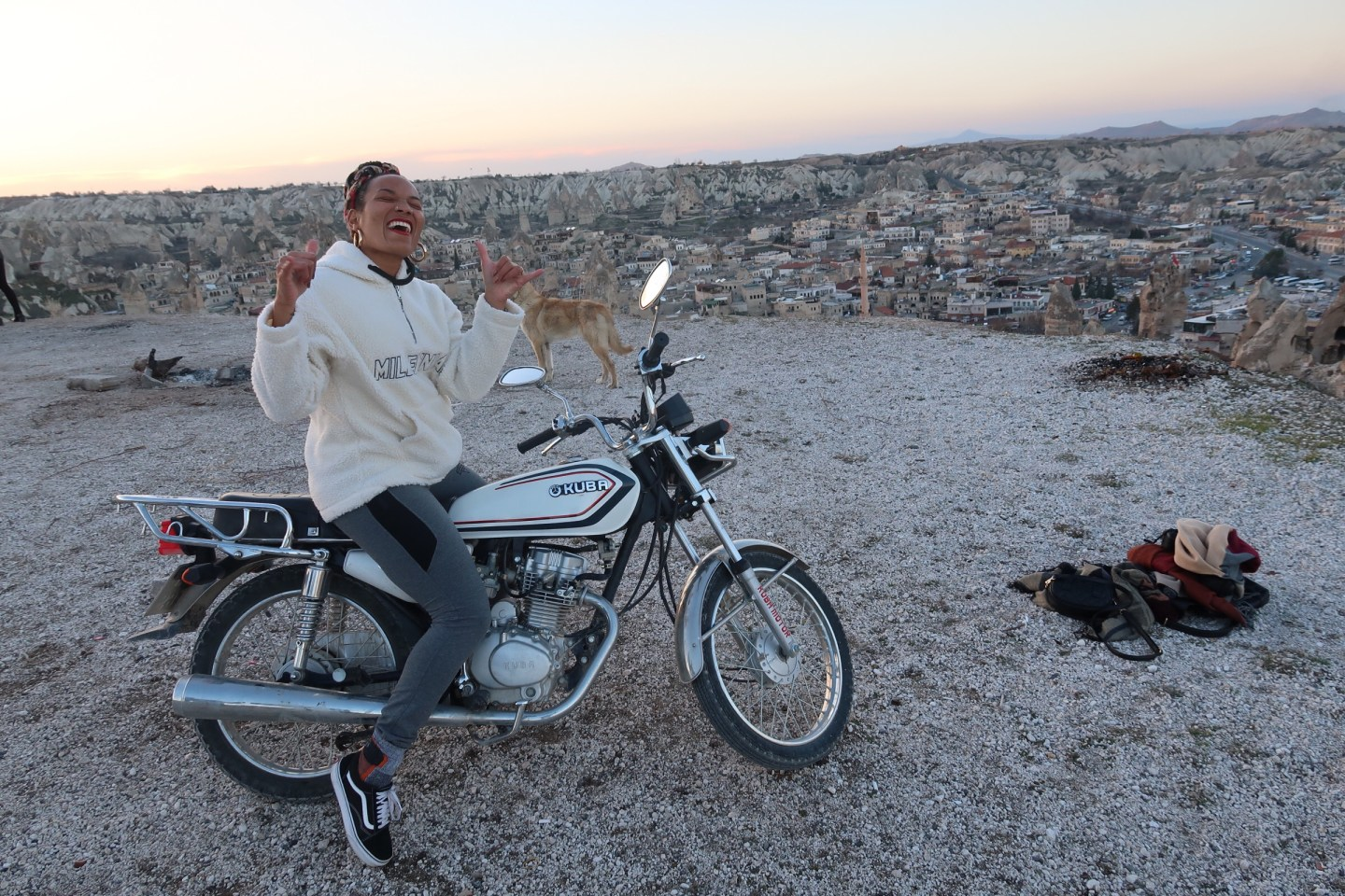 illustrated by Sade - woman riding a motorcycle on top of sunset view point in Goreme Cappadocia