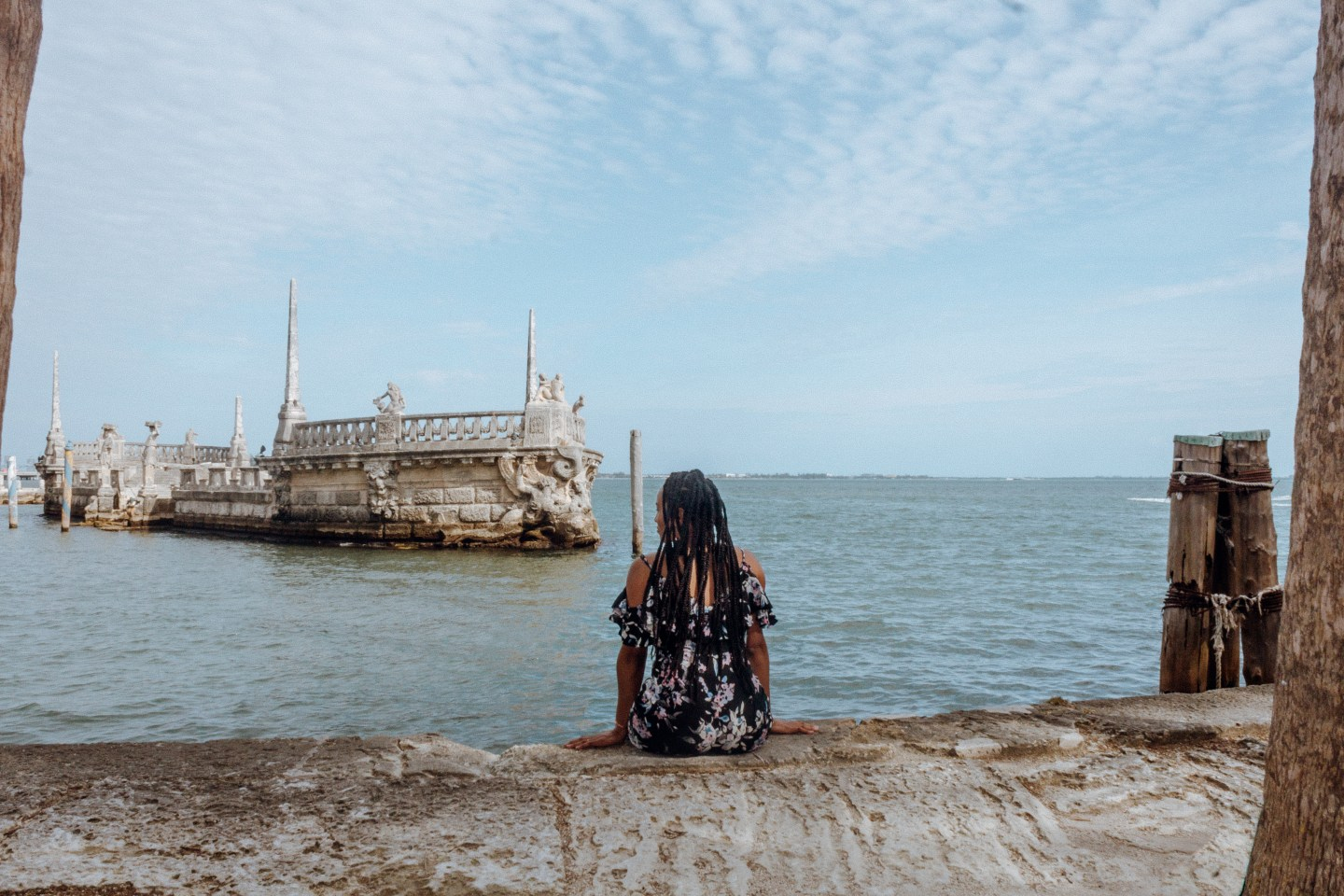 Illustrated by Sade - Woman sitting for a photo while viewing the ocean behind Vizcaya Museum and Gardens in Key Biscayne, Florida.