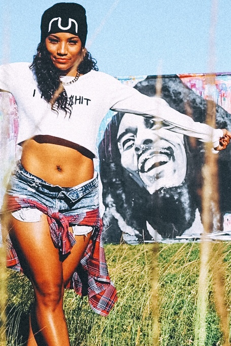 Illustrated by Sade - Woman taking a photo in front of a graffiti art mural of Bob Marley in Wynwood.
