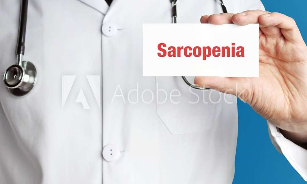 Sarcopenia. Doctor holds a business card in his hand. Text is on the sign. Close up.