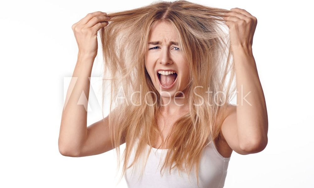Young blond woman unhappy with her haircut, touching her hair with both hands and looking at camera with screaming grimace. Front portrait on white background