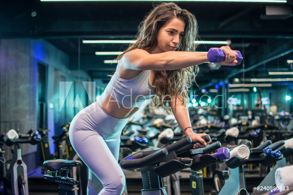 Attractive young woman training with dumbbells on cycling class at gym