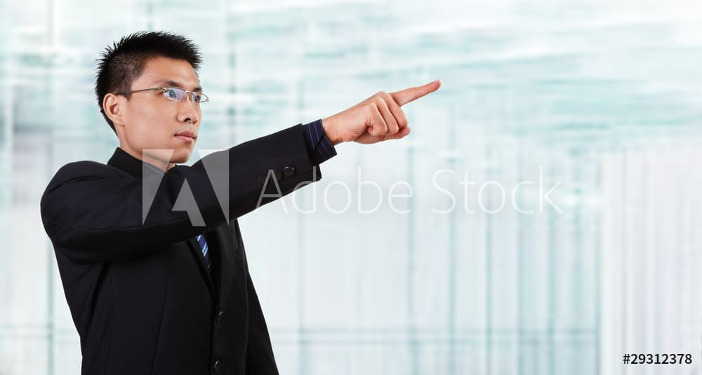 Chinese businessman pointing to empaty space