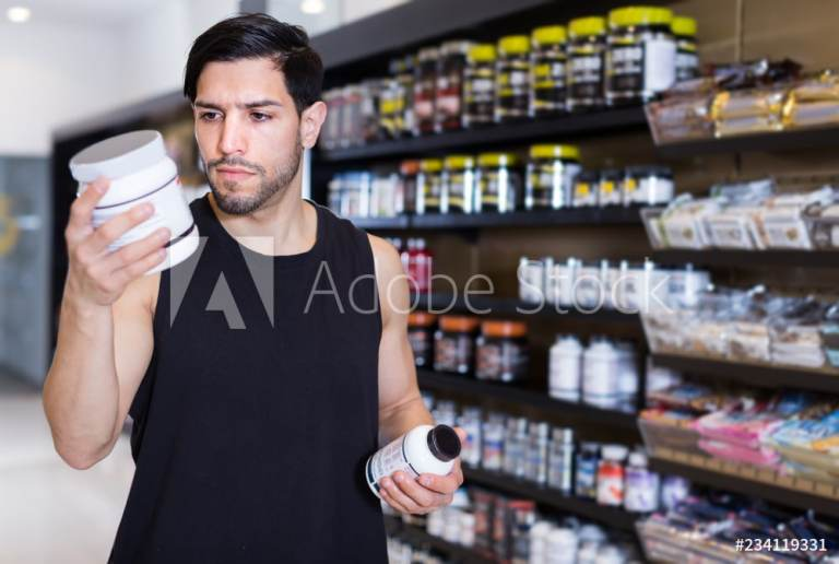 Young muscular sportman looking sport dietary supplements in store