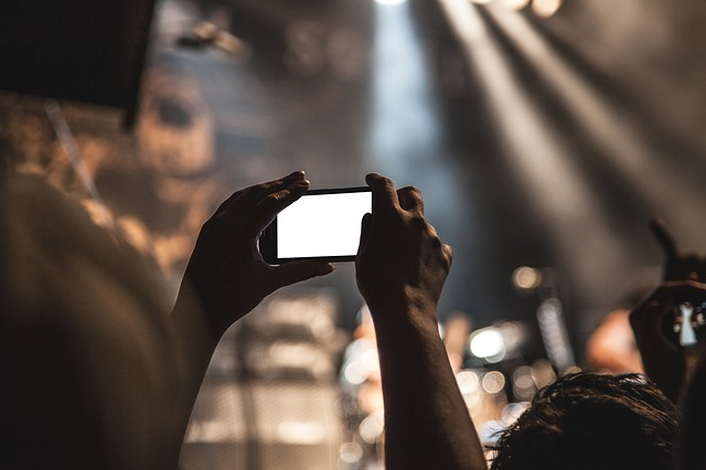 mani che tengono un smartphone che scatta una foto