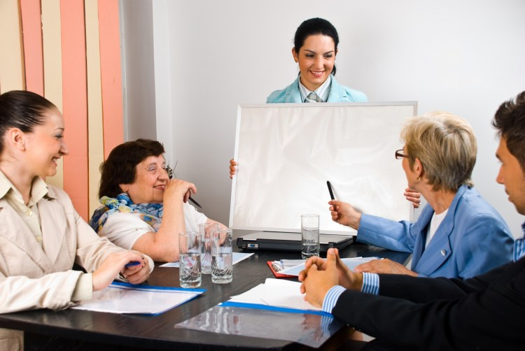 Five people of various ages meeting around a table.  One woman is holding a chart and another is gesturing toward the chart.     <!-- HTML Credit Code for Can Stock Photo -- data-recalc-dims=