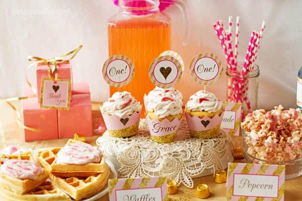 baby girl first birthday pink and gold party decorations table with recipes for waffles, pink cupcakes , popcorn.