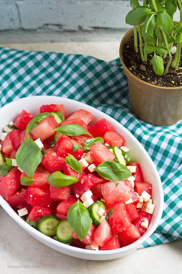 Salads with fruit, feta, sliced cucumber and basil.