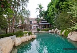 A piscina é cercada de pedras e árvores