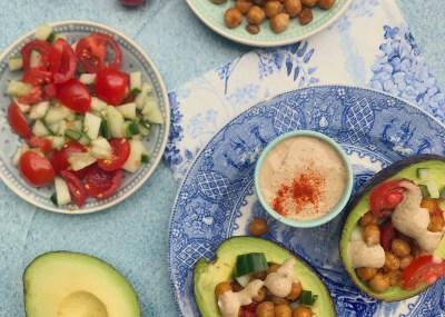 Gezonde vegan lunch: Gevulde avocado met geroosterde kikkererwten, komkommer, tomaat en romige tahinsaus