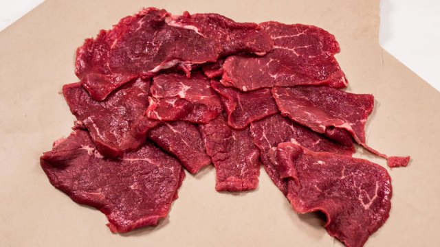 Pile of thin sliced beef eye of round laying on a sheet of butcher paper.
