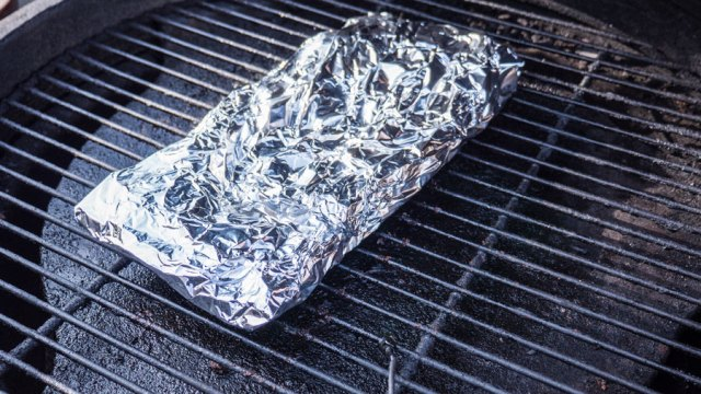 rack of ribs wrapped in aluminum foil sits on the grill grate of a Big Green Egg.