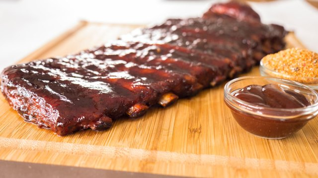 Shiny glazed rack of St.Louis spare ribs lays on a cutting board along side a small cup of bbq rub and bbq sauce.