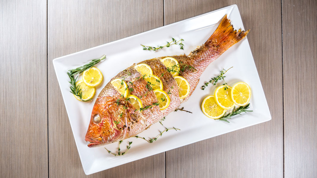 Grilled Red Snapper on a plate with lemons and rosemary.