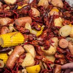 Large pile of cooked crawfish and vegetables.