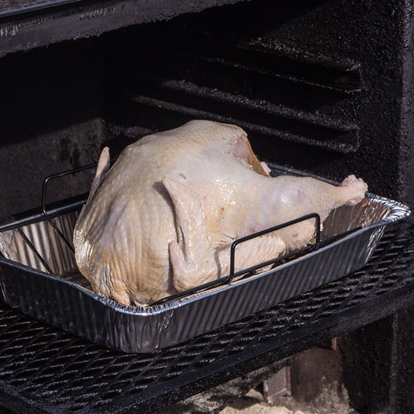 Turkey sitting in an aluminum pan being smoked.