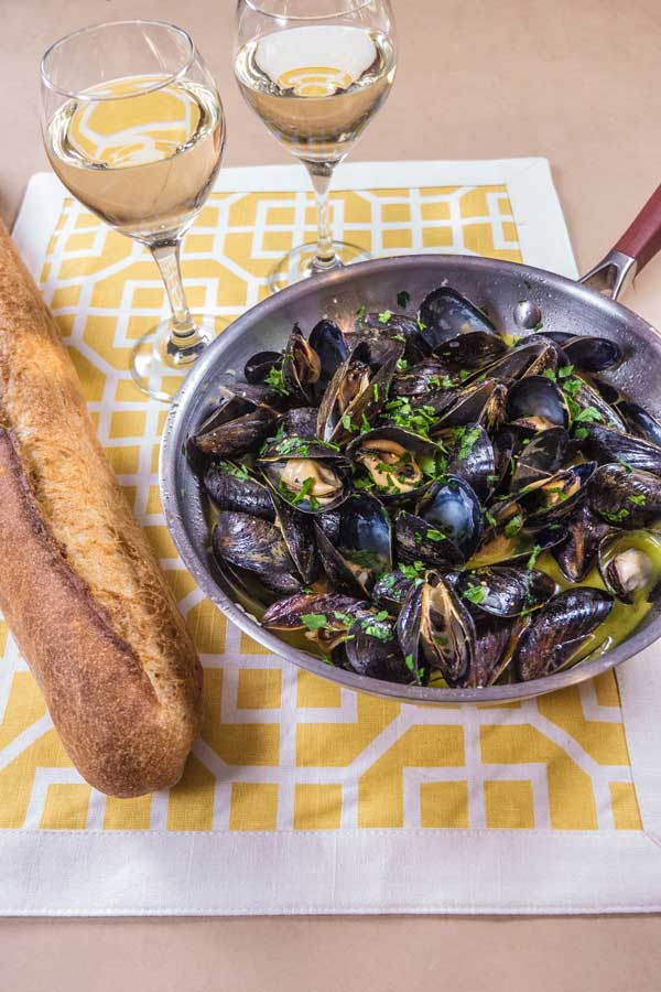 two glasses of white wine and a skillet of mussels